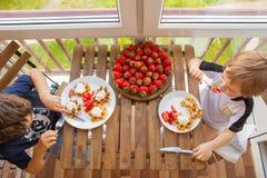两个男孩吃着奶蛋烘饼用草莓和冰淇凌 图库摄影