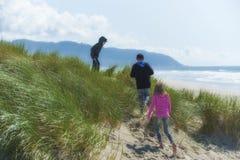 两个男孩和女孩探索在海滩的沙丘 免版税图库摄影