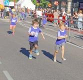 两个男孩和女孩赛跑 库存图片