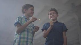 两个男孩在一间发烟性被放弃的屋子 有一次灼烧的比赛的,第二一个男孩与一个灼烧的打火机 股票录像