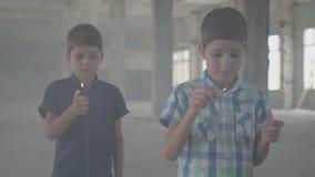 两个男孩在一间发烟性被放弃的屋子 有一次灼烧的比赛的,第二一个男孩与一个灼烧的打火机 股票视频