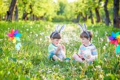 两个男孩在公园,获得乐趣用复活节的色的鸡蛋 图库摄影