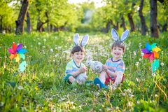 两个男孩在公园,获得乐趣用复活节的色的鸡蛋 免版税库存照片
