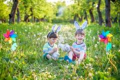 两个男孩在公园,获得乐趣用复活节的色的鸡蛋 库存照片