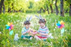 两个男孩在公园,获得乐趣用复活节的色的鸡蛋 免版税图库摄影