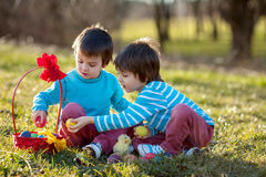 两个男孩在公园,获得乐趣用复活节的色的鸡蛋 库存图片