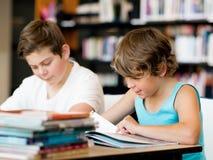 两个男孩在图书馆里 免版税库存图片
