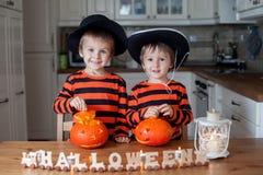 两个男孩在家,南瓜为万圣夜做准备 免版税库存图片