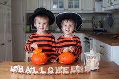 两个男孩在家,南瓜为万圣夜做准备 免版税库存照片