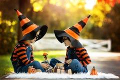 两个男孩在有万圣夜服装的公园,获得乐趣 库存照片