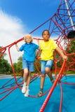 两个男孩在网红色绳索一起站立  免版税图库摄影