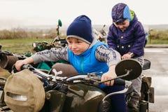 两个男孩坐一辆老单轮摩托车 图库摄影