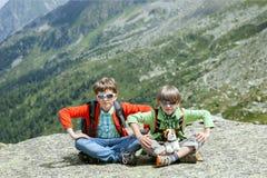 两个男孩坐在峭壁顶部 免版税库存图片