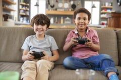 两个男孩坐沙发在一起打电子游戏的休息室 库存图片