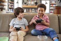 两个男孩坐沙发在一起打电子游戏的休息室 图库摄影