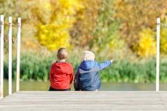 两个男孩坐码头 秋天 回到视图 免版税库存照片