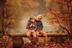 两个男孩坐长凳由池塘 免版税库存图片