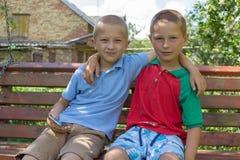 两个男孩坐长凳,两个兄弟拥抱坐长凳 库存照片