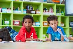 两个男孩孩子在地板和读书在preschoo的传说书放下 免版税库存照片