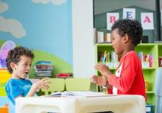 两个男孩孩子坐桌和着色在书在学龄前图书馆里,幼儿园学校教育概念 免版税库存图片