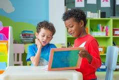 两个男孩孩子坐桌和读书传说书在学龄前解放 免版税图库摄影