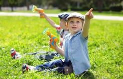 两个男孩孩子画象坐草使用 图库摄影
