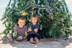两个男孩庆祝在海滩的圣诞节 库存照片