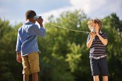 两个男孩戏剧锡罐电话 免版税库存图片