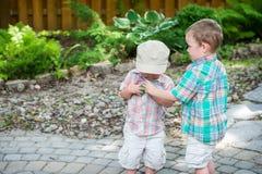 两个男孩收集五颜六色的复活节彩蛋 免版税库存照片