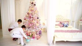 两个男孩新年` s礼物在从他们的儿子的圣诞树下为父母做准备在明亮的卧室自白天 股票录像
