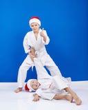 两个男孩是训练的柔道摔在圣诞老人盖帽 库存图片