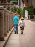 两个男孩沿城市河走 免版税库存照片