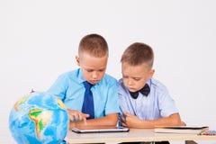两个男孩看互联网片剂学校 库存照片