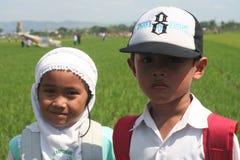 两个男孩看见了在稻碰撞的训练航空器 免版税库存图片