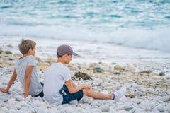 两个男孩紧挨着坐海滩由海 免版税库存照片