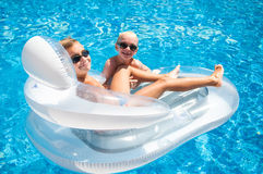 两个男孩获得使用在一个浮动床垫的乐趣在游泳 免版税库存图片