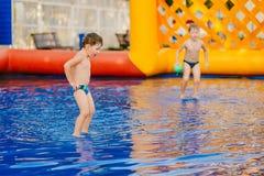 两个男孩踢在一个可膨胀的室外水池的水橄榄球 库存照片