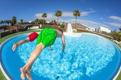 两个男孩采取倒栽跳水入水池 库存图片