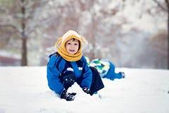 两个男孩,兄弟,使用在与雪球的雪 库存图片