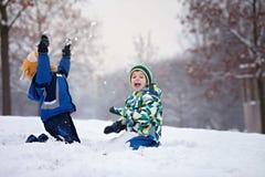 两个男孩,兄弟,使用在与雪球的雪 免版税图库摄影