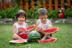 两个男孩,吃西瓜在庭院里,夏令时 免版税库存照片
