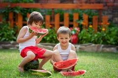 两个男孩,吃西瓜在庭院里,夏令时 库存照片