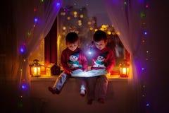 两个男孩,在窗口的阅读书 免版税库存照片