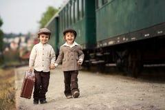两个男孩,打扮在葡萄酒衣物和帽子,带着手提箱 免版税图库摄影