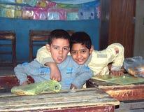 两个男孩画象坐他们的盘 库存照片