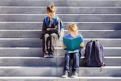 两个男孩读,做家庭作业户外 回到概念学校 免版税图库摄影