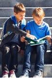 两个男孩读,做家庭作业户外 回到概念学校 免版税库存图片