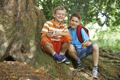 两个男孩Geocaching在森林地 库存照片