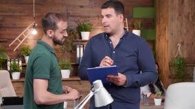 两个男性同事站立和谈话在现代舒适办公室 影视素材