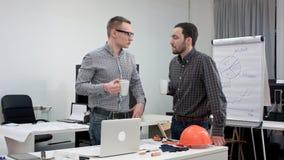 两个男性工友有咖啡休息和谈话在办公室 免版税库存图片